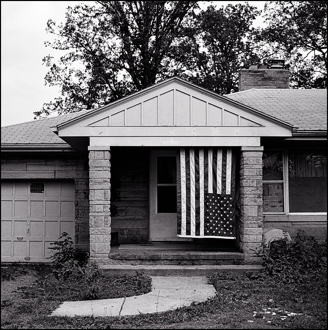 An American flag hangs upside down from the front porch of an abandoned house in Fort Wayne, Indiana.