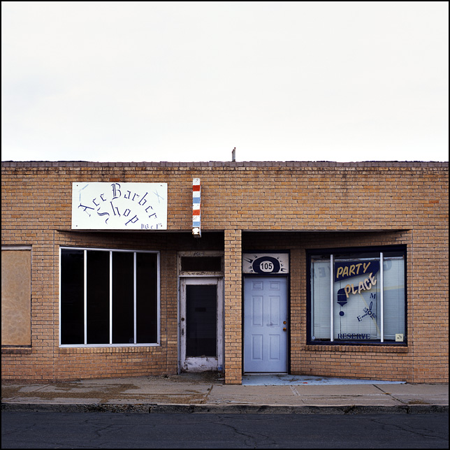 Two abandoned storefronts in an old yellow brick building in Roswell, New Mexico. One of them is Ace Barber Shop and the other is NM Party Place.
