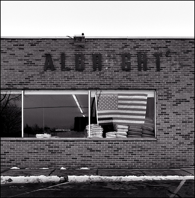 A large American flag hangs in the front window of Albright's Meats in the small town of Corunna, Indiana. Some letters are missing from the sign on the old brick storefront.