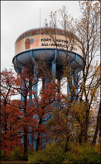 An old rusty water tower on the east side of Fort Wayne, Indiana. The tower has a faded American flag and the title Fort Wayne All-America City painted on it.