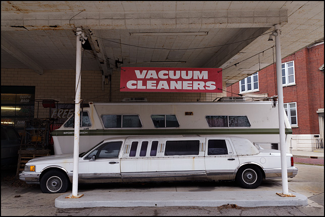 A beat-up old Lincoln Town Car stretch limousine with flat tires and an old motorhome are parked under a banner advertising vacuum cleaners in front of Allen County Sweeper Company on Broadway in Fort Wayne, Indiana.