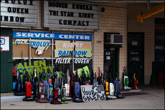 A bunch of used vacuum cleaners stand on the sidewalk in front of the Allen County Sweeper Company on Broadway in Fort Wayne, Indiana.