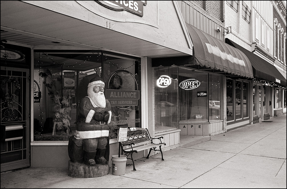 Aa hand carved wooden Santa Claus sculpture stands in front of Alliance Tax Service on High Street in the small town of Hicksville, Ohio.