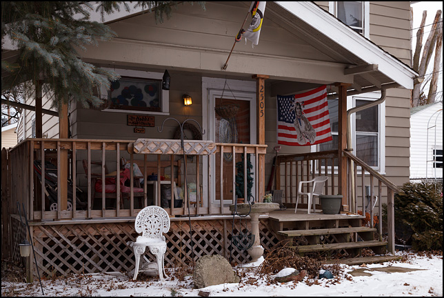 An American flag with a Native American printed on it hangs on the front porch of a house on Crescent Avenue in Fort Wayne, Indiana.