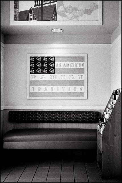 "A sign that looks like the American flag with coffee cups for stars hangs over a bench in the entryway of an IHOP restaurant. The sign says ""An American Family Tradition."""