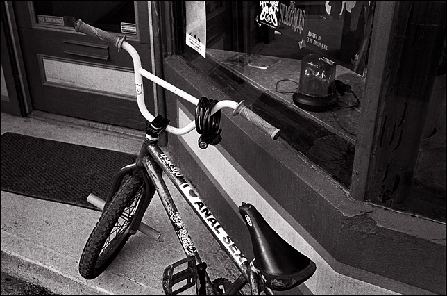 A 20 inch BMX bicycle that has a big sticker on it that says I LOVE ANAL SEX. The bike is leaning against the front door of Cardinal Tattoo Shop on Spy Run Avenue in Fort Wayne, Indiana.