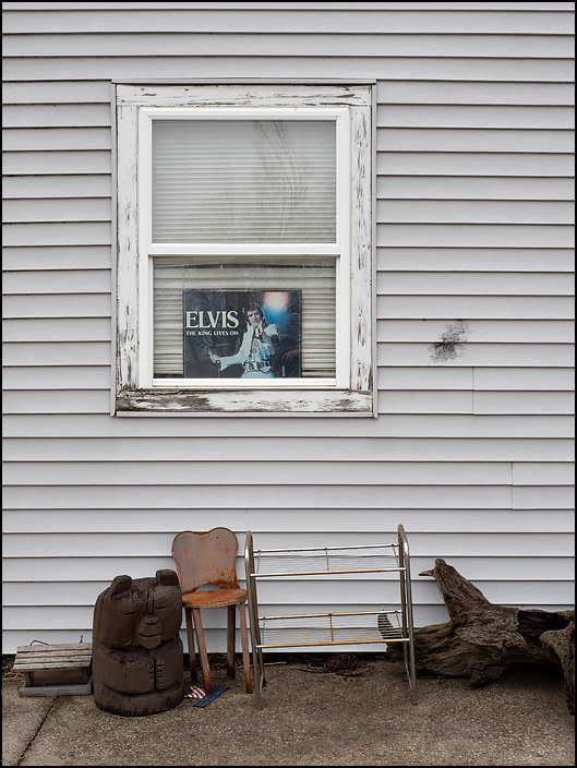 An Elvis Presley sign in the front window of a small house on Main Street in the small town of Andrews, Indiana. The sign says Elvis The King Lives On. A wooden bear carved from a log sits on the sidewalk under the window.