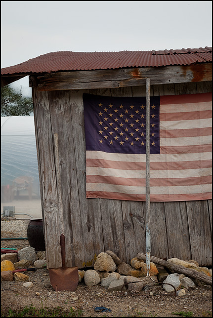 Faded old American flag tacked to the weathered wooden siding on a small storage shed at Back Porch Flea Market on US-24 near Andrews, Indiana.