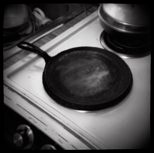 Toy camera photograph of an old cast iron skillet sitting on the stove.