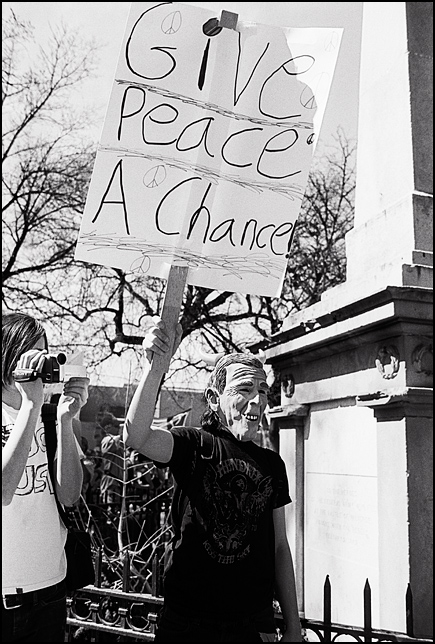An antiwar activist protests for peace on the Santa Fe plaza wearing a George W. Bush mask on the anniversary of the war in Iraq. His sign says Give peace a chance.