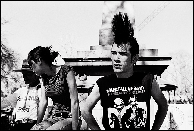 "A young man with a Mohawk hairstyle watches the antiwar protest at the Santa Fe Plaza that marked the anniversary of the beginning of the Iraq War. His t-shirt says ""Against All Authority."""