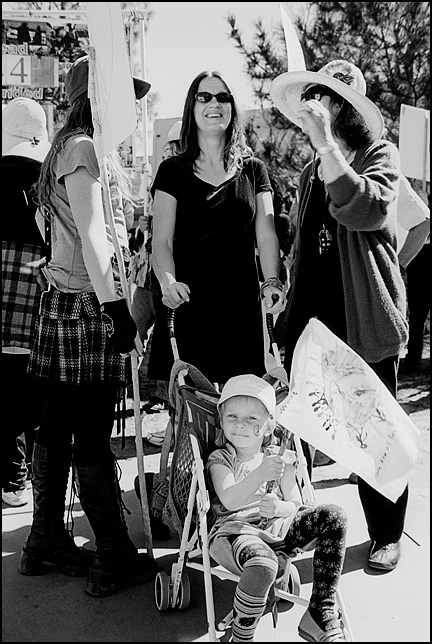 A little girl in a stroller waves a flag showing the world surrounded by people of all colors while her mother talks to other antiwar activists on the Santa Fe Plaza during the protest on the anniversary of the start of the Iraq War.