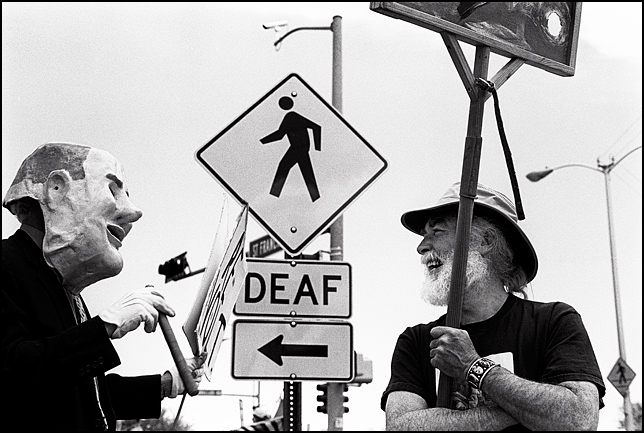 An antiwar activist dressed as a fatcat businessman with a huge cigar talks to another peace protestor at a rally in Santa Fe. They are standing in front of a Deaf sign on the street.