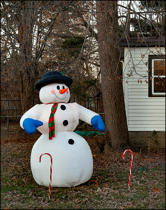 An inflatable snowman and large plastic candy canes stand in the front yard of a house on Arbor Avenue in Fort Wayne, Indiana. Fall leaves cover the ground around them.