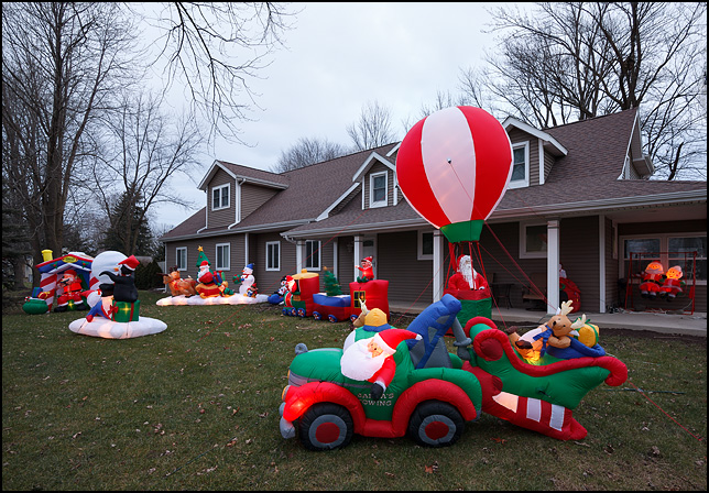 A yard full of inflatable Christmas decorations in front of a house on Ardmore Avenue in Fort Wayne, Indiana. The display includes a Santa house, Santa in a hot air balloon, Santa towing his sleigh behind a wrecker, a Santa Train, and several snowmen and penguins.