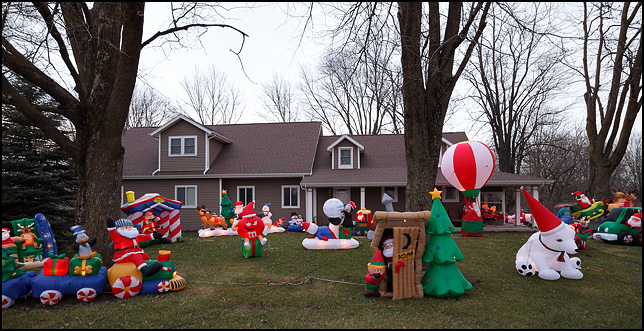 huge number of inflatable christmas decorations cover the front yard of a house on ardmore avenue