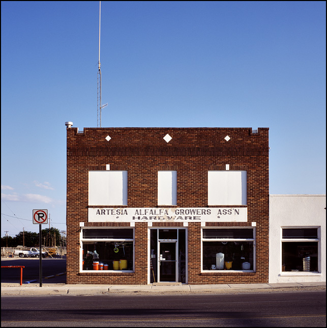 A two story brick storefront with the Artesia Alfalfa Growers Association Hardware store in Artesia, New Mexico. A tall antenna tower stands on top of the building.
