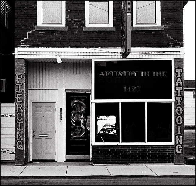 The abandoned Artistry In Ink Tattoo Shop in an old brick storefront on Wells Street in Fort Wayne, Indiana. A real estate agent's sign hangs in the window and other signs on the building say Tattooing and Piercing.