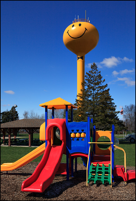 The yellow smiley face water tower in the small town of Ashley, Indiana. A playground stands in front of the water tower in Memorial Park.