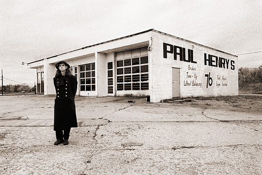 Self portrait of fine art photographer Christopher Crawford wearing a Soviet Russian Army overcoat in front of the abandoned gas Paul Henry's 76 Gas Station at the corner of Bluffton Road and Ferguson Road in Allen County, Indiana.