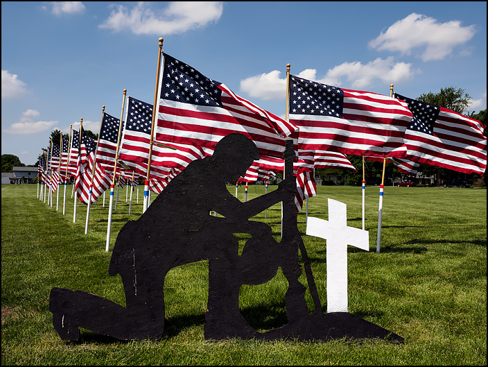 On Memorial day, American flags cover the grounds of Immaculate Conception Catholic Church in the small town of Auburn, Indiana. A plywood silhouette of a kneeling soldier and a cross stands in front of the flags.