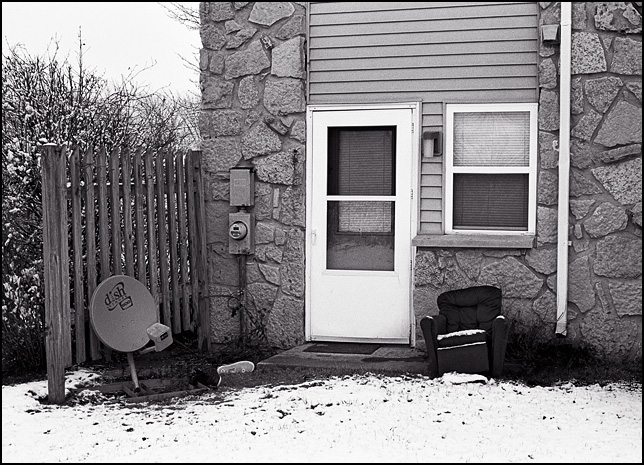 A child sized recliner chair sits covered in snow next to the back door of an apartment building in Waynedale.