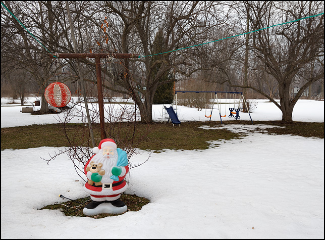 A plastic Santa Claus stands in the snow in front of a clothesline pole and a swing set in an old woman's back yard in Fort Wayne, Indiana.