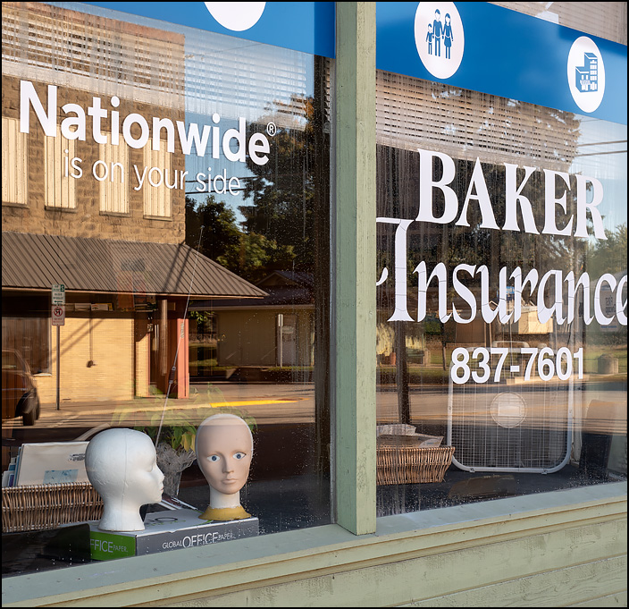 Two styrofoam mannequin heads in the front window of Baker Insurance Agency on Wayne Street in the small town of Waterloo, Indiana.
