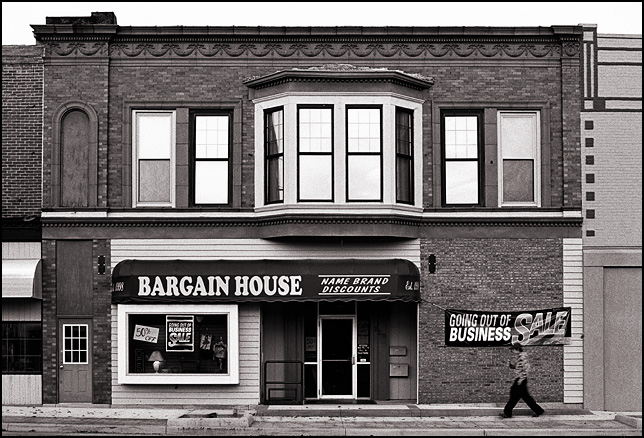 A man walks past signs and banners advertising a going out of business sale on the Bargain House, a store on Main Street in the small town of Churubusco, Indiana.