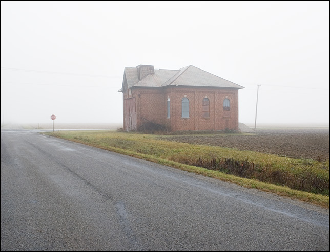An abandoned brick one-room schoolhouse at a rural Indiana crossroads on a foggy winter morning. It is on the corner of Barkley road and Fackler Road in southeast Allen County.