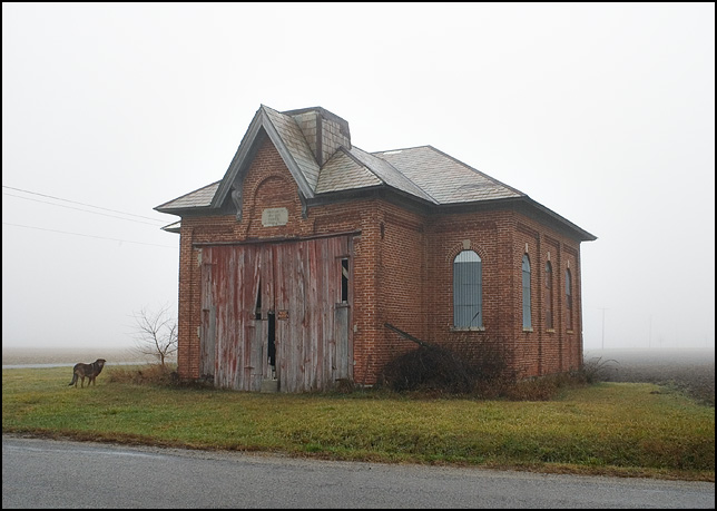 A dog stands in front of an abandoned brick one-room schoolhouse on a foggy winter morning. The schoolhouse, which has been used as a barn, is on the corner of Barkley Road and Fackler Road in rural southeast Allen County, Indiana.