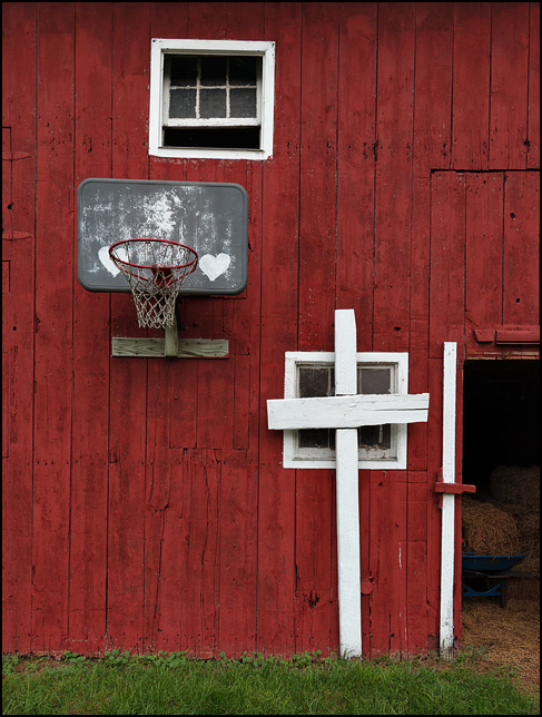 A red barn with a basketball hoop and a big white cross on State Road 1 in Leo-Cedarville in rural Allen County, Indiana. The basketball backboard has white hearts painted on it.