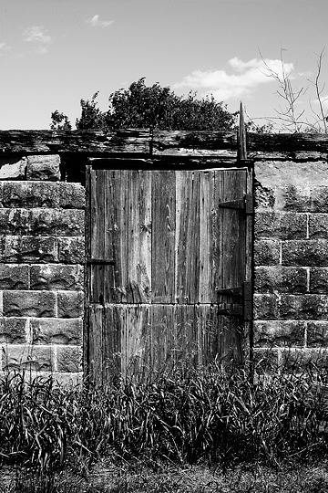 The weathered wood dutch doors on the ruins of an old cinderblock barn with no roof in rural Pulaski County, Indiana.