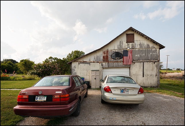 A barn used as a garage with an American flag and a basketball hoop hanging over the door in rural Allen County, Indiana.
