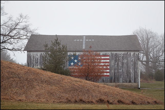 An old weathered barn behind a hill on Rapp Road in rural Allen County, Indiana. The roof has a cross design built into the shingles, and there is a large American flag painted on the side.