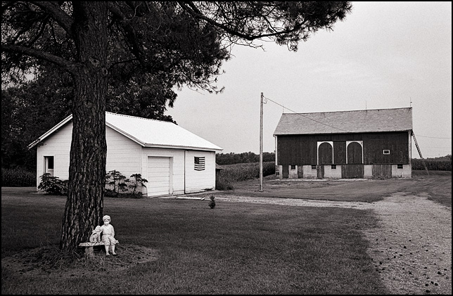 A large barn, a garage with an American flag hanging on it, and a tree with a statue of a boy and a dog sitting in front of it, in the yard behind a farmhouse in rural Allen County, Indiana.