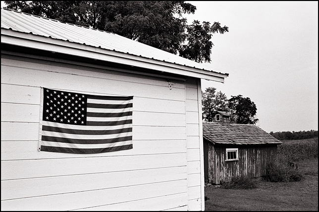 A white garage with an American flag hanging on the door next to an old chicken coop in rural Allen County, Indiana.
