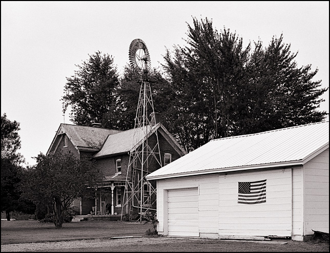 A garage with an American flag stands behind an old brick farmhouse and windmill on US-24 in rural Allen County, Indiana.