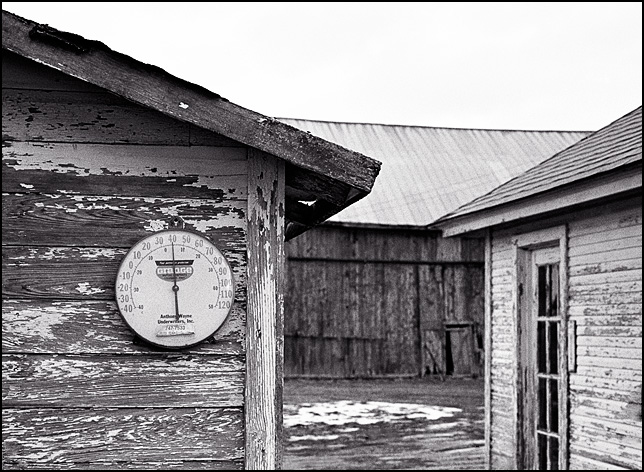 A dial thermometer with the Grange Insurance logo hanging on the side of an old weathered wood storage shed on an abandoned farm in Indiana.