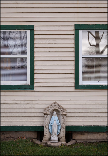 A painted concrete statue if the Virgin Mary stands in a concrete alcove decorated with roses in front of a house on Barthold Street on the working-class northwest side of Fort Wayne, Indiana.