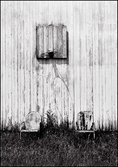 A pair of old rusty metal motel chairs sit in tall grass by an abandoned barn under a basketball hoop at an abandoned farm on Till Road in rural northwest Allen County, Indiana.