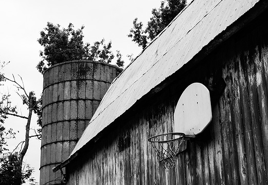 A basketball hoop hanging on the side of an old weathered barn with a concrete silo and tin roof in rural Pulaski County, Indiana.