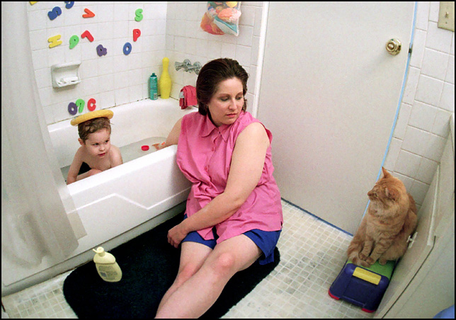 My sons mother gives him a bath while a fat orange cat watches.
