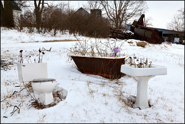 Snow covers dead flowers growing in an old toilet, bathtub, and sink in the front yard of a farmhouse in Indiana during the winter.