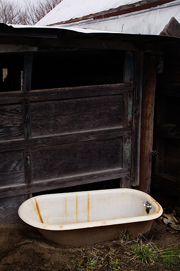 An old cast iron bathtub on the ground in front of a garage on an abandoned farm in Indiana.