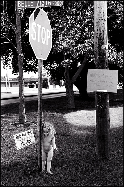 A large naked doll stands under a stop sign at the corner of Old Trail Road and Belle Vista Boulevard. A yard sale sign is nailed to a utility pole next to her.
