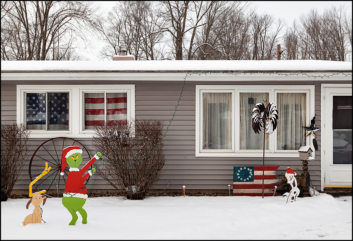 A hand-painted plywood Grinch stealing the Christmas lights from a house on Allendale Drive in the Belle Vista neighborhood in Fort Wayne, Indiana. The house has a large American flag covering two of the front windows, and a handpainted American flag next to the front door.