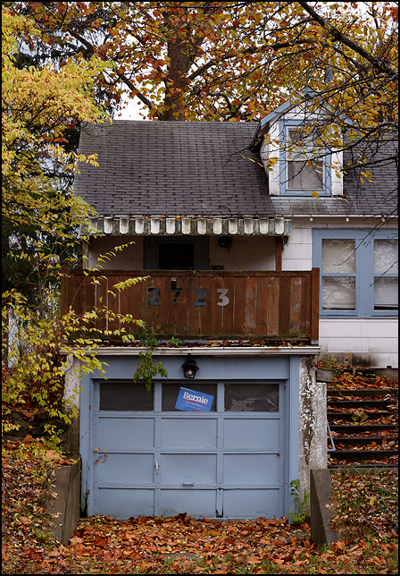 A Bernie Sanders sign in the window on the garage built into the side of a hill under the house that stand atop the hill. It is on Wells Street in Fort Wayne, Indiana.