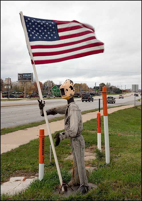 A welded steel sculpture of a welder holding a large American flag stands along Lima Road in front of Berrys Welding in Fort Wayne, Indiana.