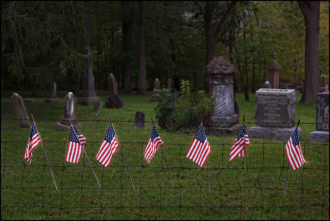 Several small American flags hang in the fence at Bethel Cemetery on Winchester Road in Allen County, Indiana.